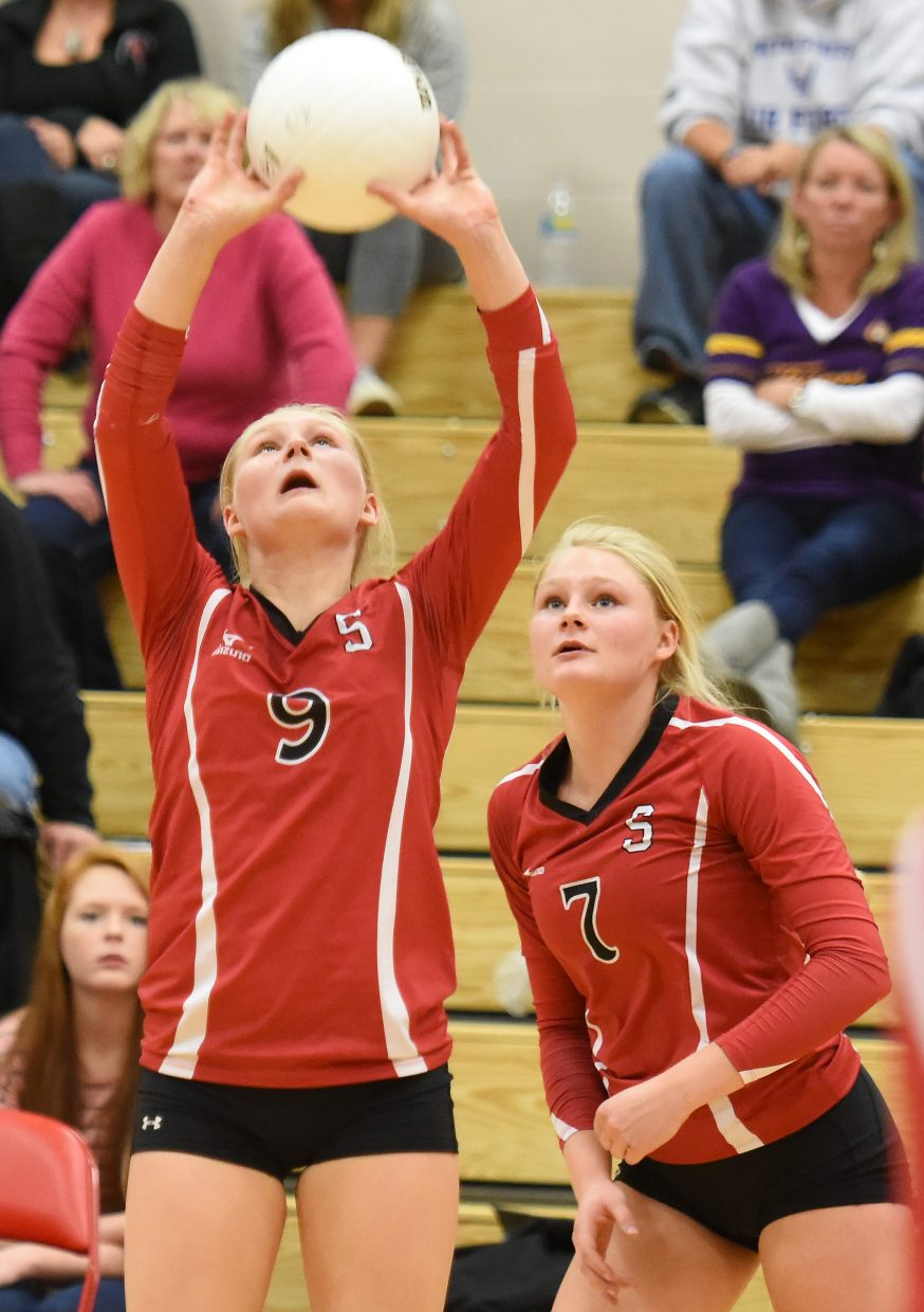 Abigail Wiedel, left, next to her twin sister Maritza, sets the ball in a game last fall for the Sailors.