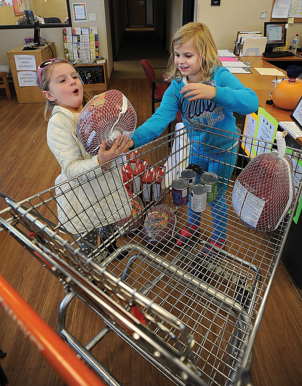 Makena James, left, and friend Ava Ford load food they bought into a cart at LIFT-UP of Routt County. The girls earned the money at a lemonade stand they ran in September and wanted to use it to buy Thanksgiving turkeys and trimmings to donate to the local food bank. The girls also raised money last winter caroling and plan to purchase gifts for the cancer ward at Children's Hospital this holiday season.