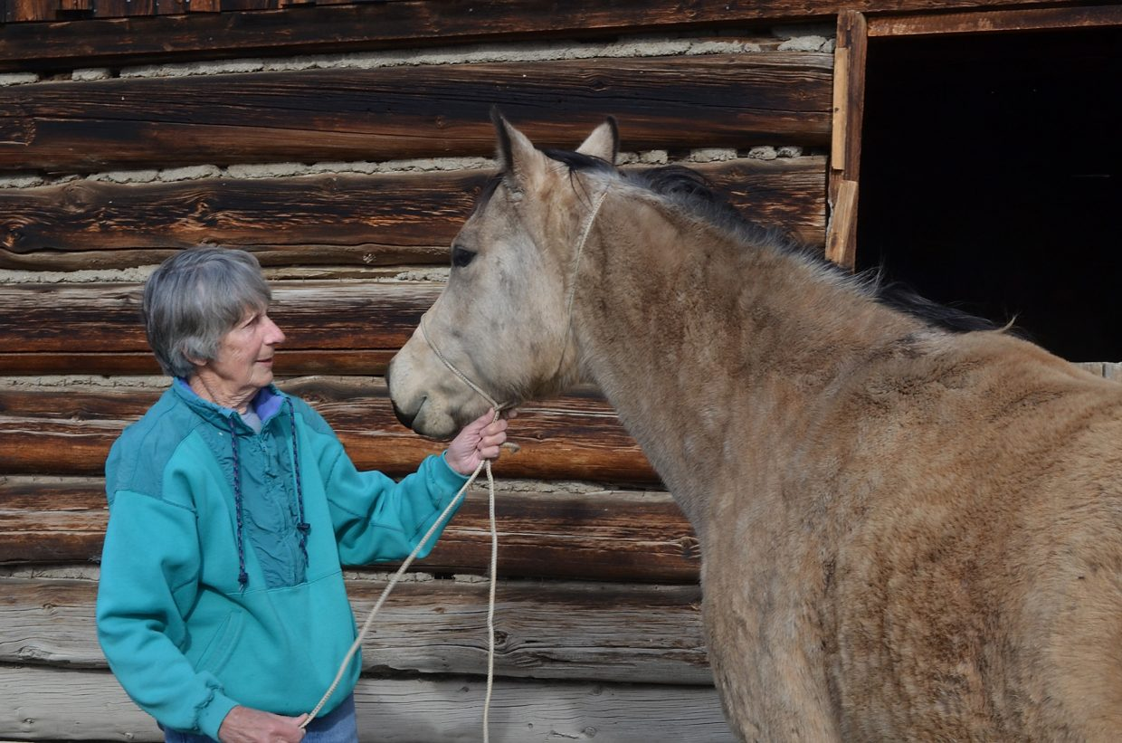 Wanda Redmond and her buckskin mare, Dolly, are the best of friends. The log barn in the background is on the Routt County and Colorado registers of historic places.