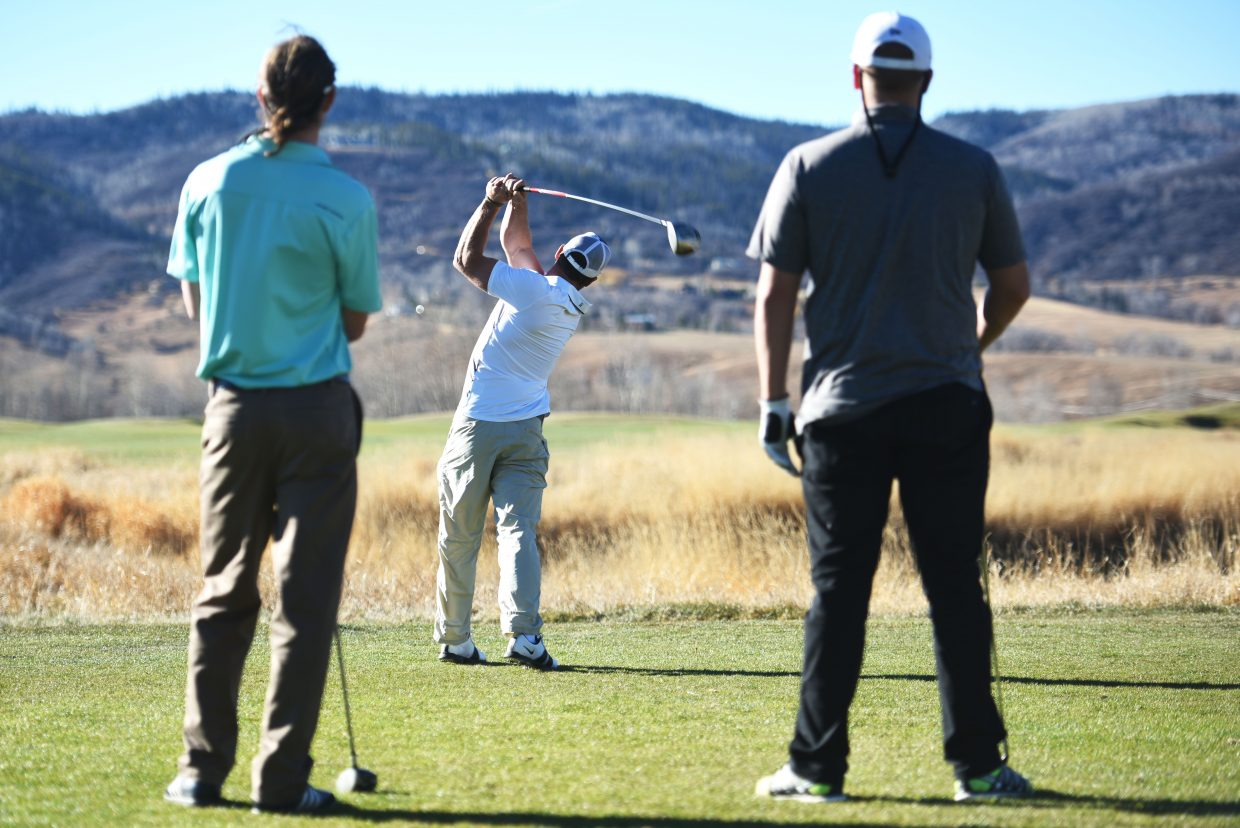 Travis Garner tees off Wednesday afternoon at Haymaker Golf Course while Luke Kimmes, left, and Aaron Kinslow wait for their turn. The course is still open, the last course open in Steamboat Springs, though managers said the first dusting of snow may be enough to finally end the season.