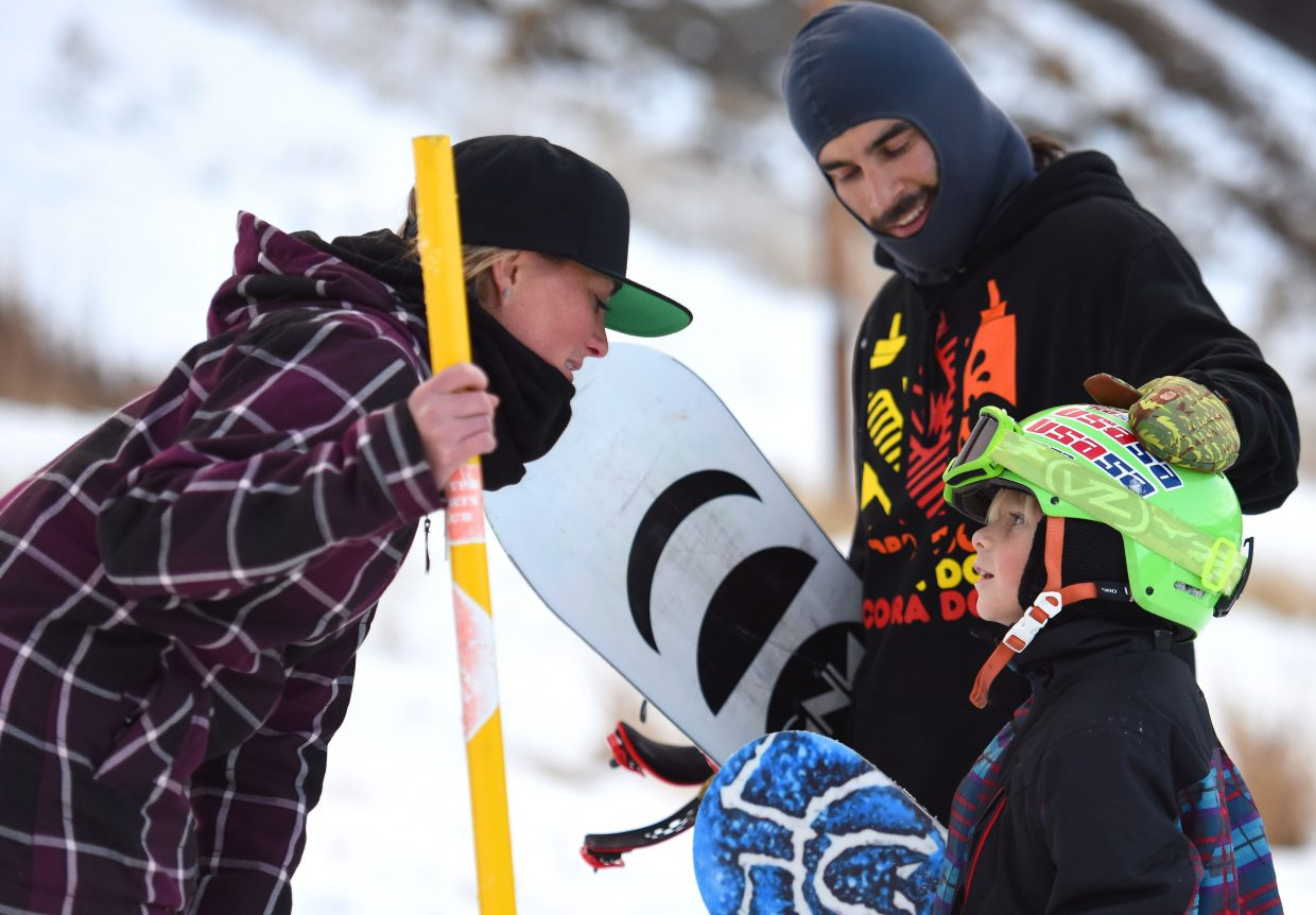 Winter Sports Club snowboard director Tori Koski, left, and coach Al Grogan offer a bit of advice to 9-year old rider Brenden Duty on Tuesday at Howelsen Hill.