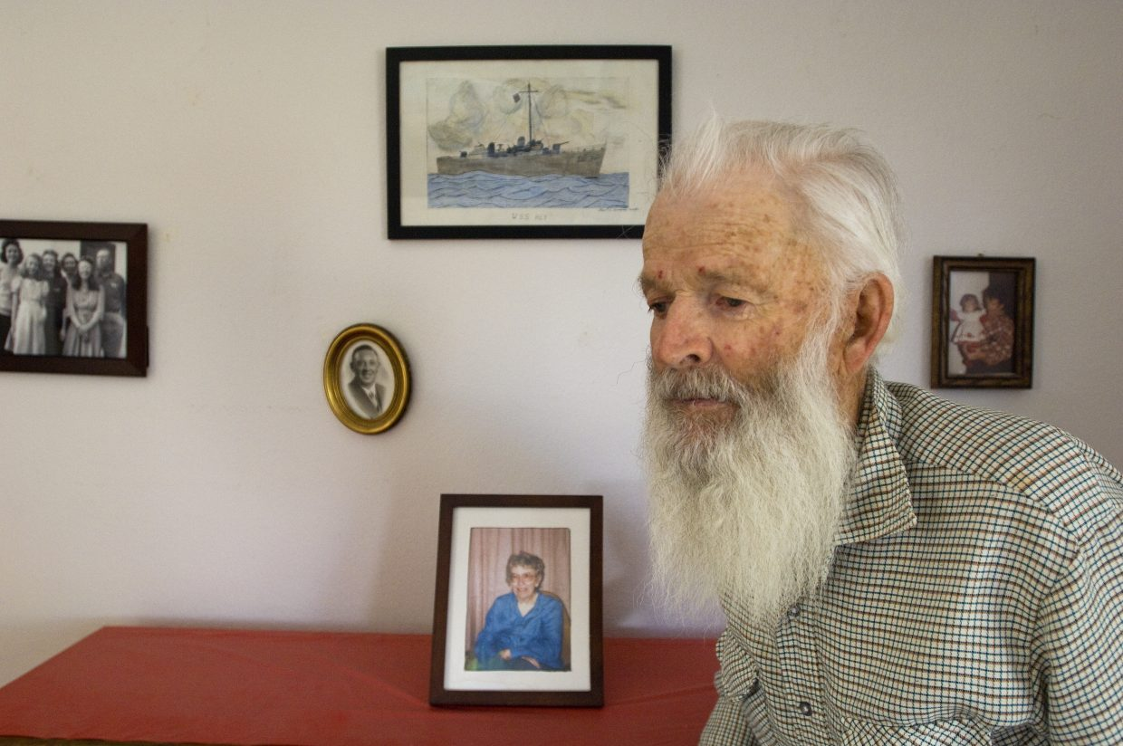 Bob Nicodemus stands before a photo of his wife, Berdena, who passed away about three years ago, and a drawing she made for him of the Navy destroyer on which he was stationed during World War II, the U.S.S. Key.