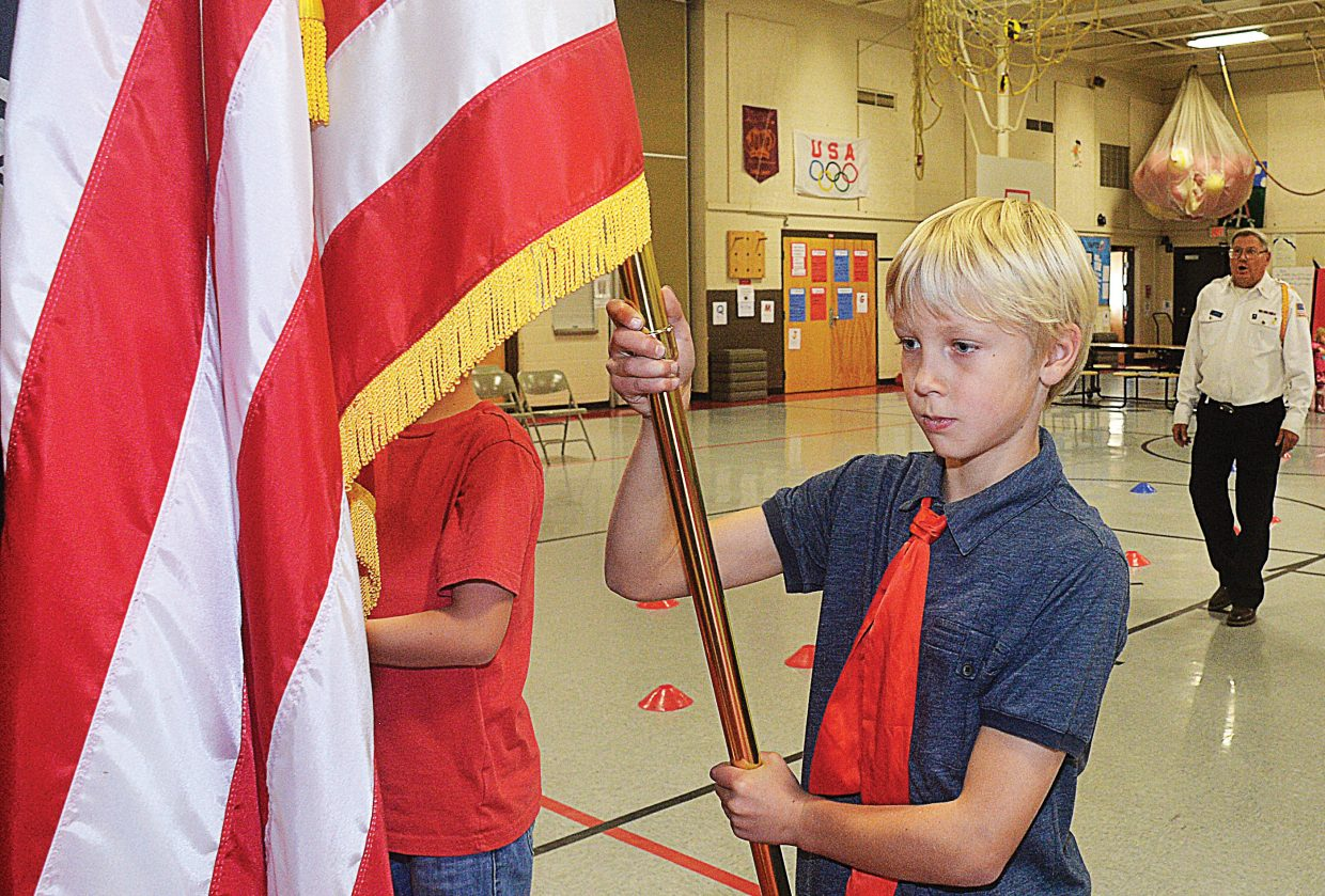 Steamboat Springs veteran Jim Stanko works with fifth-grader Xander Tatar-Brown prior to Tuesday's Veterans Day program at Strawberry Park Elementary School. Students were selected to present the flags during a special holiday program put on at the school.