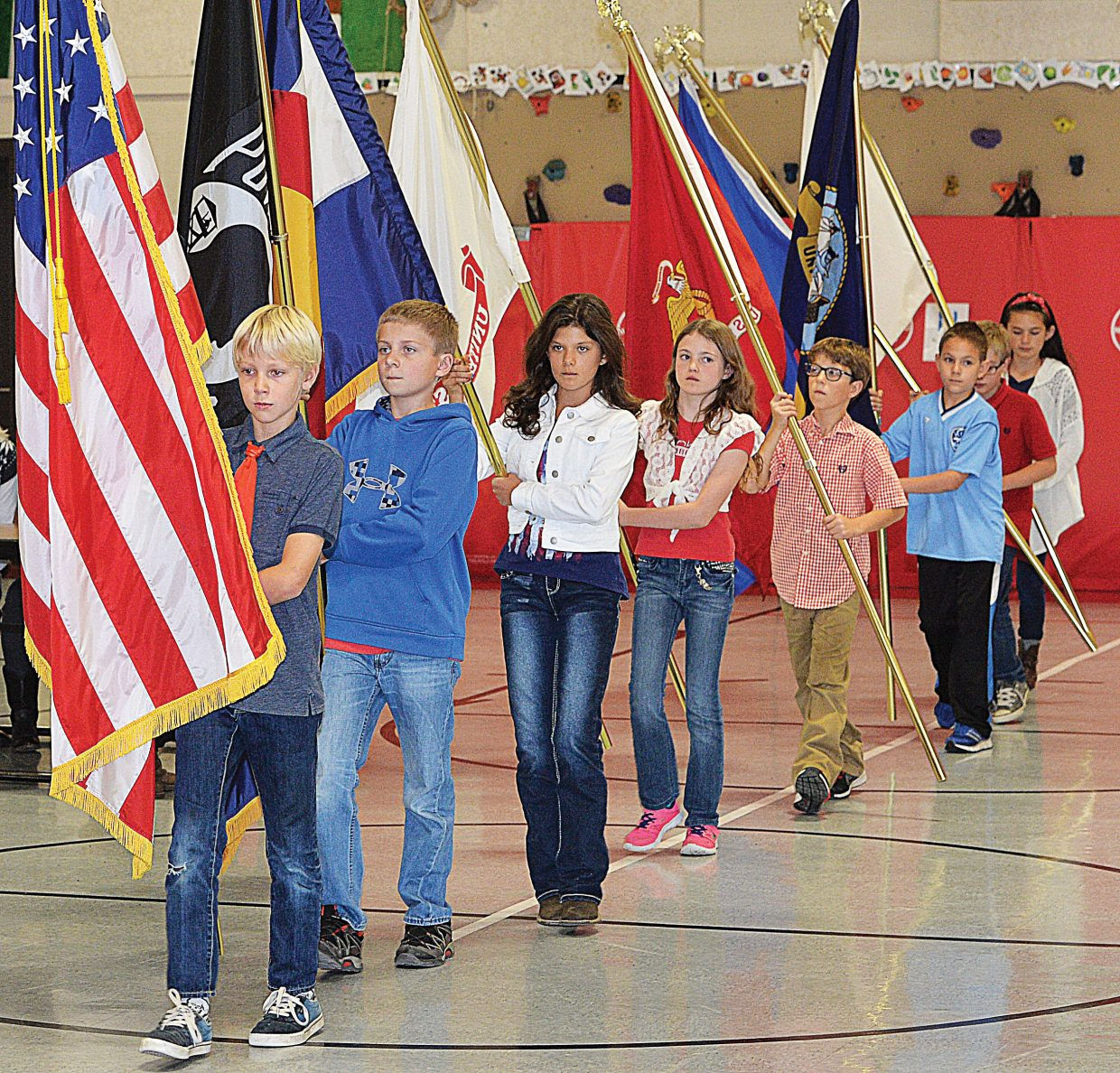 Xander Tatar-Brown and several other fifth-graders carry the flags while practicing for Strawberry Park's Veterans Day program Tuesday afternoon.