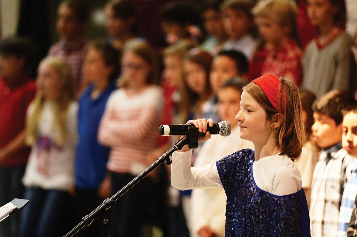 Dressed in red, white and blue, Soda Creek fifth grader Alison Apostle takes her turn in front of the microphone, reading a passage as part of a program honoring Steamboat Springs Veterans Wednesday for Veterans Day.