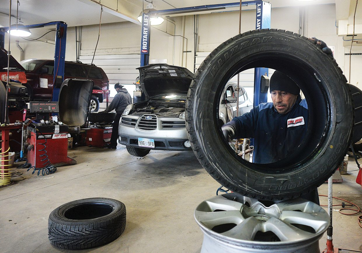 Yampa Valley Tire Pros employee Tony Scapardine works with fellow employees to change the tires on a Subaru on Thursday morning. The recent snow, and has prompted many drivers to take their cars into local garages in an effort to get ready for winter.