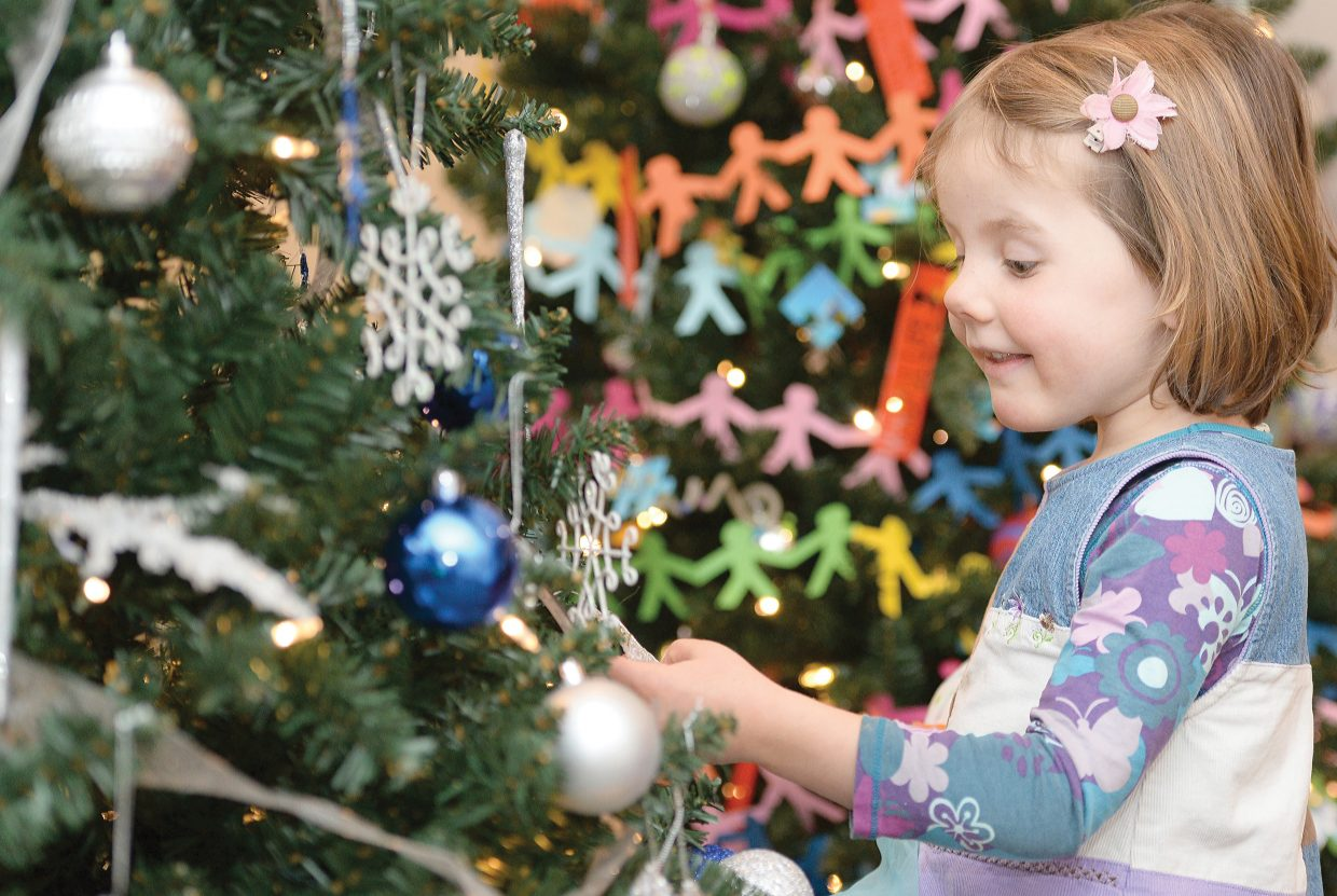 Four-year-old Leah Bannister checks out the decorations on one of the many trees inside the Tread of Pioneers Museum while her mom, Candice Bannister, executive director at the museum, takes care of last-minute details for the 2015 Festival of Trees.