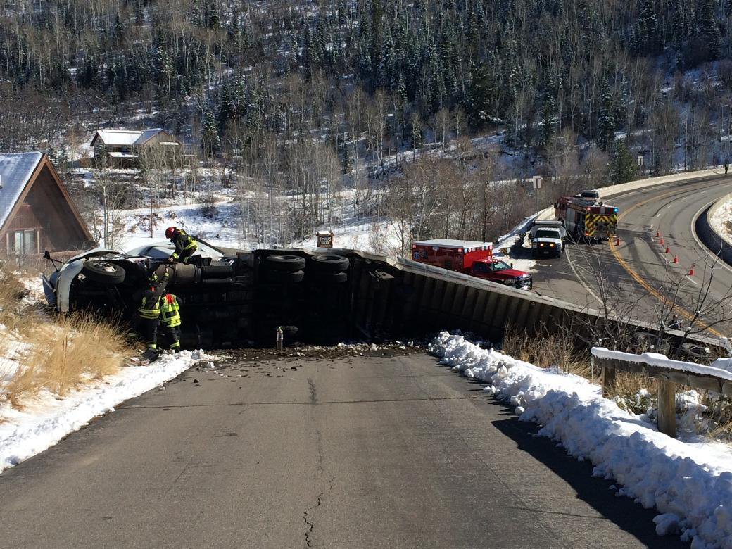 Emergency personnel work to secure the fuel tanks of a truck that was involved in a rollover accident about noon Friday near the bottom of Rabbit Ears Pass