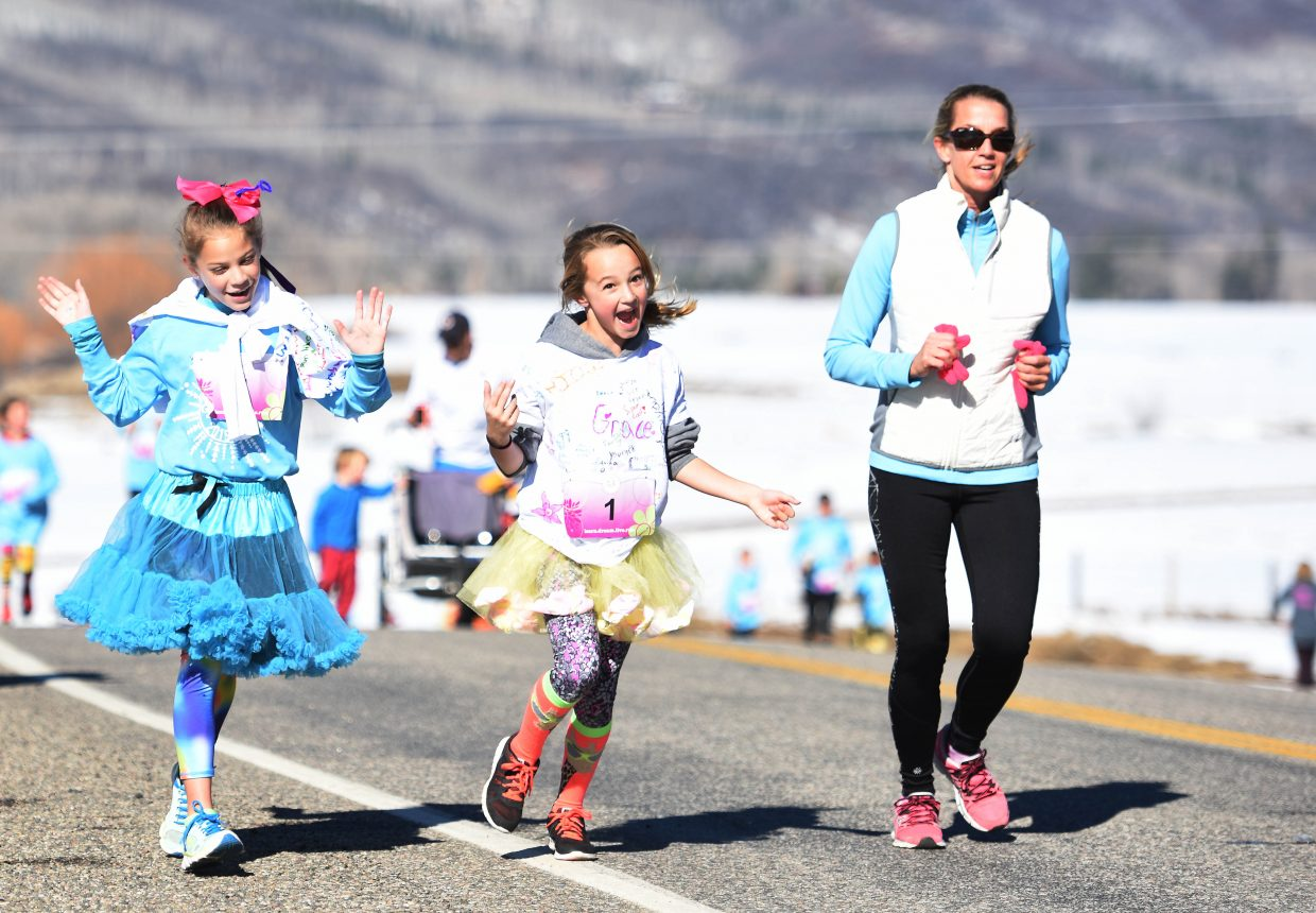 Willow Bower, left, Gracie Garcia and Susan Garcia run Saturday during the Girls on the Run event in Strawberry Park.