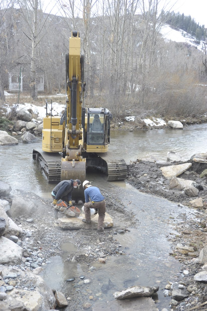 Mike Andrews, left, and Roby Hamon cut a rock along the banks of the Yampa River on Friday afternoon. The two Nordic Excavating employees are working on river improvements for the city of Steamboat Springs.