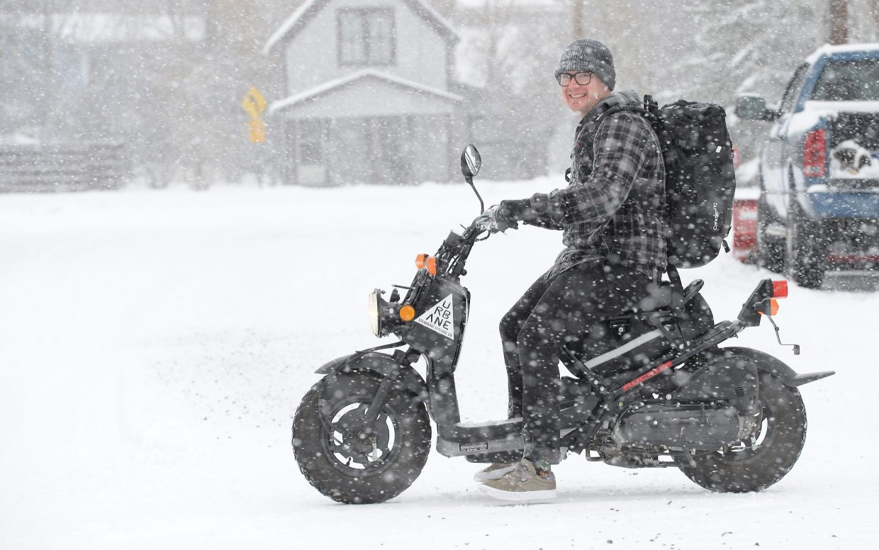 Trent Kolste rides his Honda Ruckus through the snow Monday morning. Kolste is the first to admit that the scooter wasn't made for the snowy conditions, but he said he didn't really have a choice after he rode it to work on Sunday and left it there. Kolste said he wanted to get the scooter home as soon as possible after learning that more snow is expected at the end of the week.