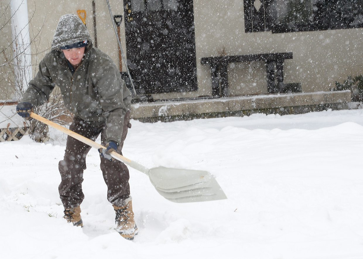 Taylor Miller shovels the walkway leading to his home on Seventh Street Monday morning. Snow arrived in bulk Monday reminding local residents that winter has arrived in the Yampa Valley.
