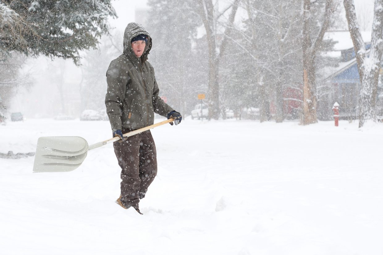 Taylor Miller shovels the walkway leading to his home on Seventh Street Monday morning. Snow came in bulk Monday reminding local residents that winter has arrived in the Yampa Valley.