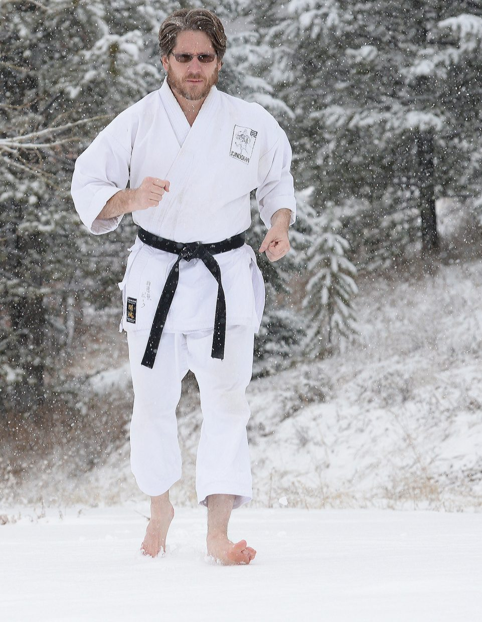 Sensei Michael David Bauk runs in the snow Monday morning as part of a workout to increase mental toughness. Bauk said he has made it a tradition to run barefoot on the first day the snow is deep enough and then a couple of more times during the winter. He also takes his classes at Rocky Mountain Karate Academy out to run barefoot in the snow as a way of teaching discipline.