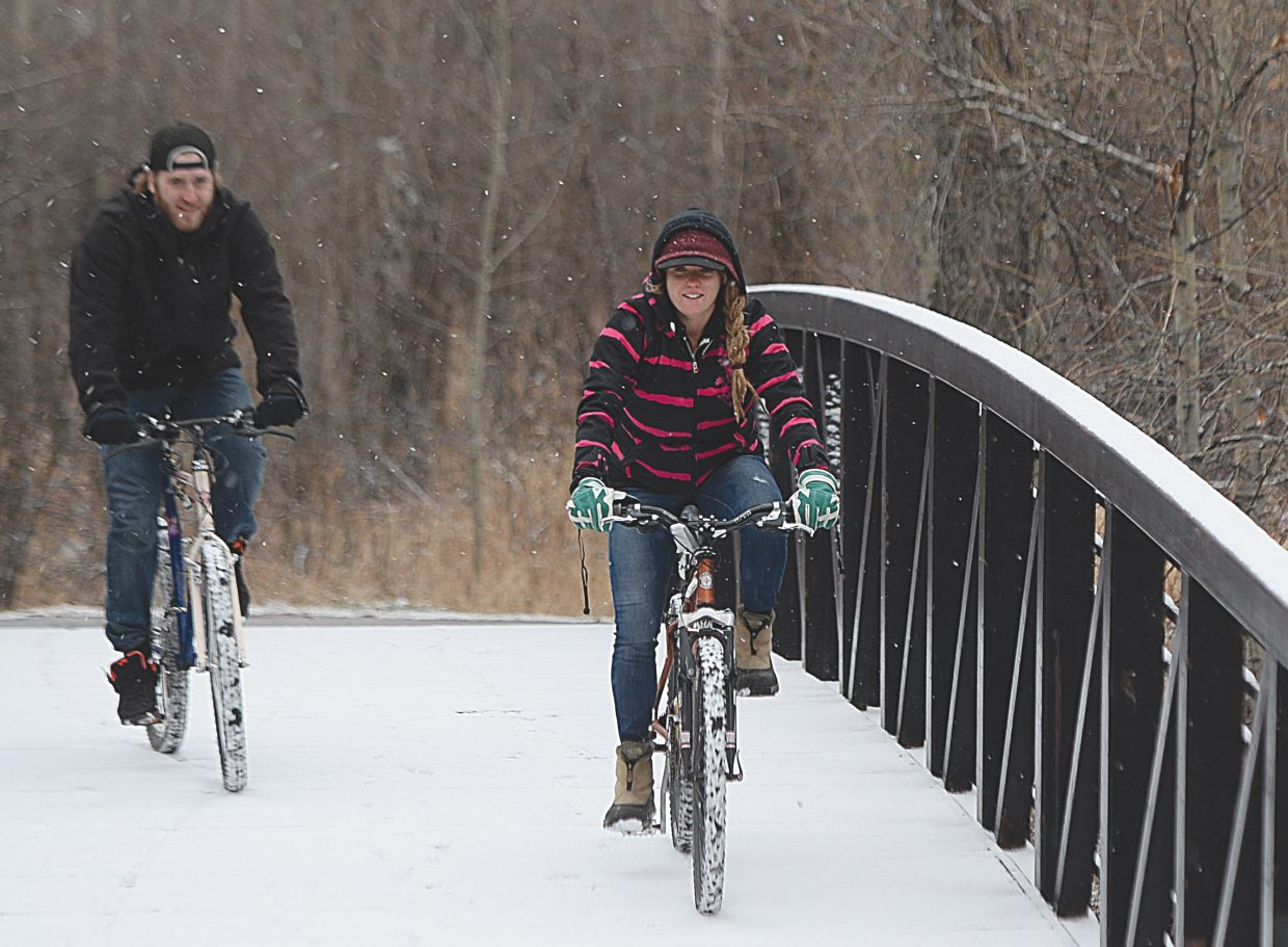Ashley Kaszynski and Brian Almer make their way along the Yampa River Core Trail Thursday afternoon. As predicted, the weather in Steamboat Springs took a wintery turn Thursday offering hope to skiers and snowboarders who are looking forward to the opening of Steamboat Ski Area's 2016-17 season.