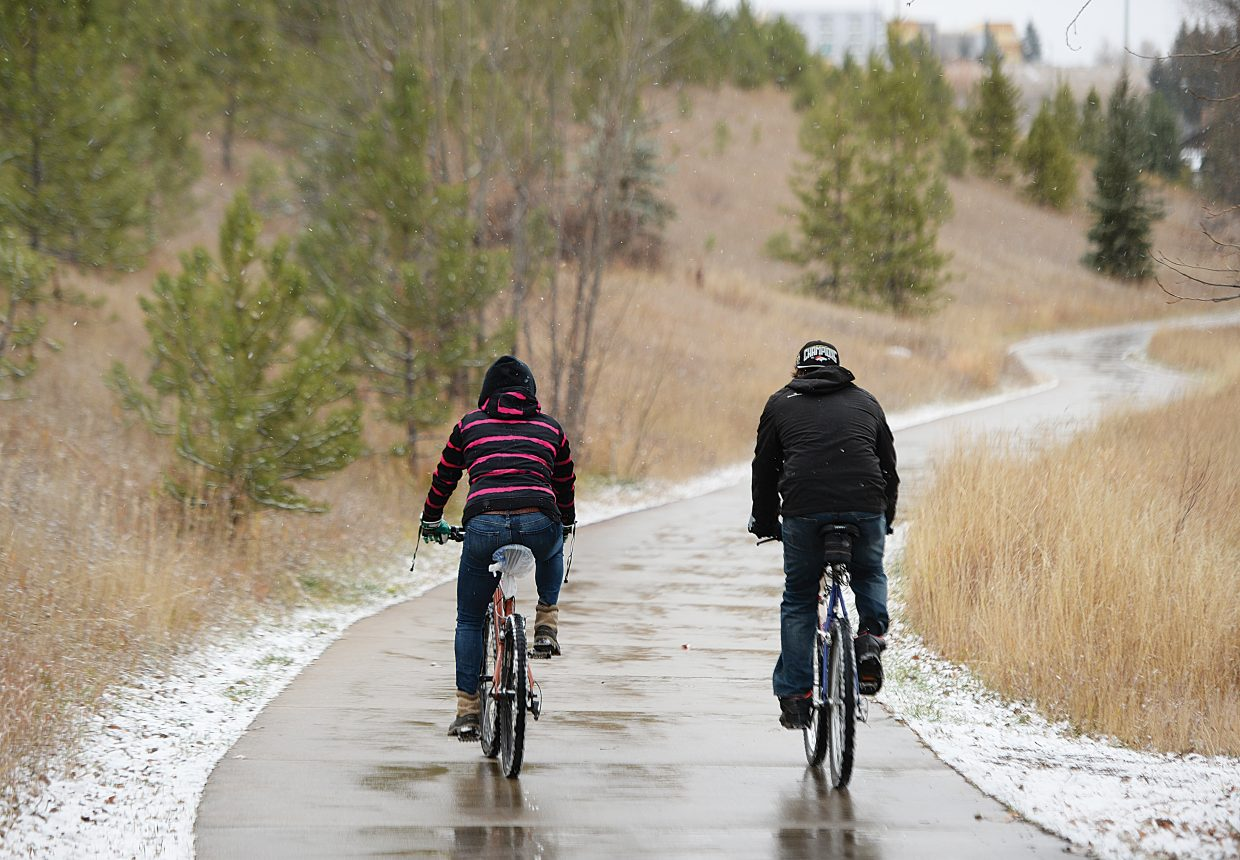 Snow can be seen falling from the sky as Ashley Kaszynski and Brian Almer make their way along the Yampa River Core Trail Thursday. As predicted, the weather in Steamboat took a wintery turn Thursday, giving hope to local skiers and snowboarders.
