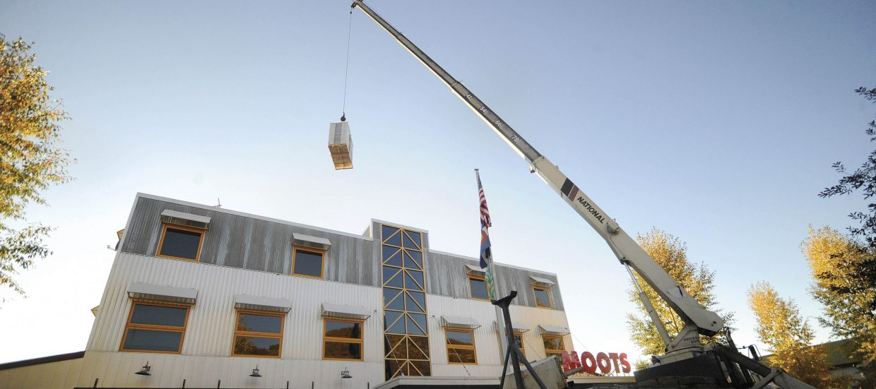 A crane is used in September 2010 to raise solar panels onto the roof of the Moots Cycles building. The solar system designed by Emerald Mountain Energy, was expected to save Moots about $1,500 in electricity costs annually at its 15,000-square-foot factory and office facility on Steamboat Springs' west side.