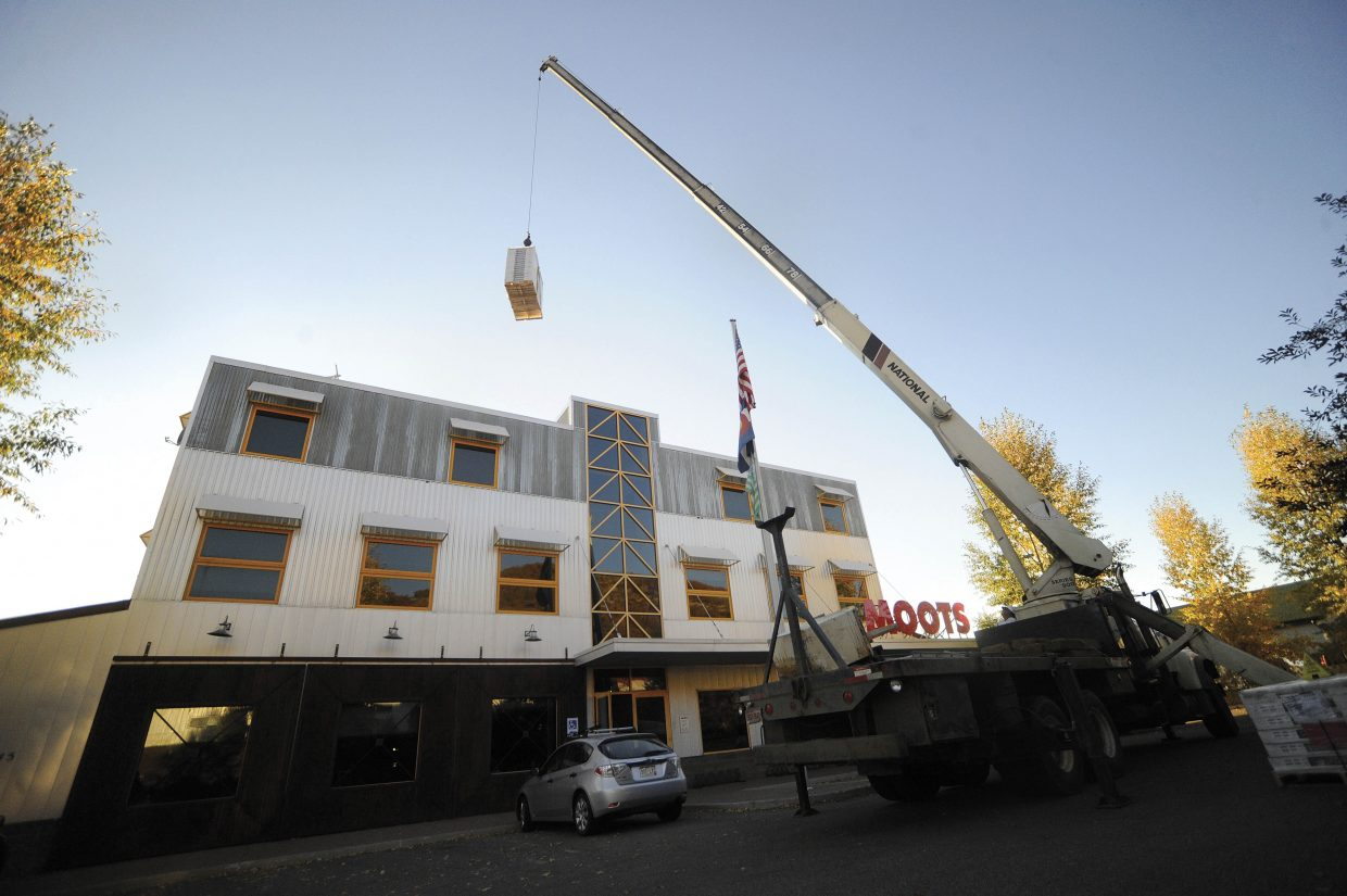 A crane is used in September 2010 to raise solar panels onto the roof of the Moots Cycles building. The system designed by Emerald Mountain Energy, was expected to save Moots about $1,500 in electricity costs annually at its 15,000-square-foot factory and office facility on Steamboat Springs' west side.
