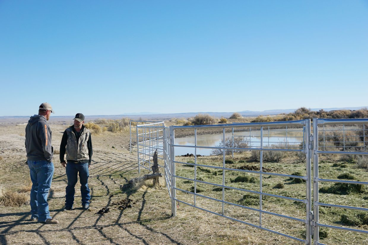 Ben Smith of the BLM discusses morning activities with one of the contractors standing beside one of the temporary traps baited with hay to tempt Sand Wash Basin wild horses in the bait and trap operation that started Nov. 9.