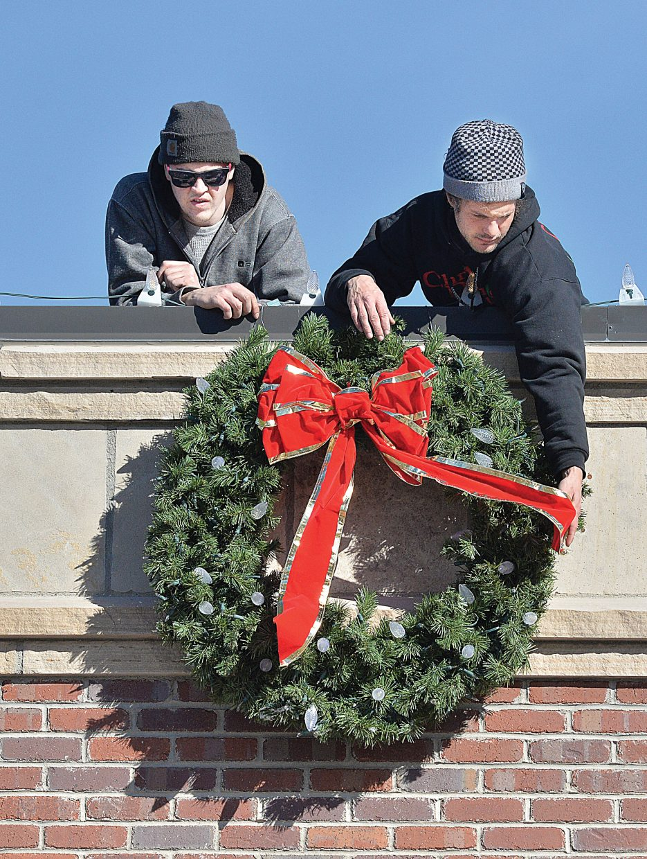 Kevin O'Neill, left, and Austin Dailey, of Christmas Decor, fasten a wreath to the top of the Steamboat Ski & Bike Kare building Friday in downtown Steamboat Springs.