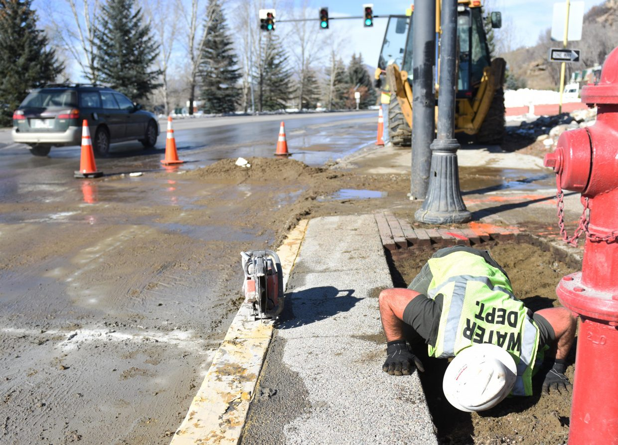 """Steamboat Springs city worker Wyatt Pierce tries to take a peak underground Saturday morning at the corner of 13th Street and Lincoln Avenue in downtown Steamboat while investigating a water main break. Kyle Higgins, with the water department, said the main broke early Saturday morning, and rushing water, quickly turning to ice, covered the west end of Lincoln in a """"nightmare scenario."""" Crews were able to isolate the problem, however, and only turned off water to one small collection of stores on Lincoln. They pulled up bricks from the sidewalk — they had to be saved because they can't be replaced —then cut into the road and dug down to find and repair the break."""