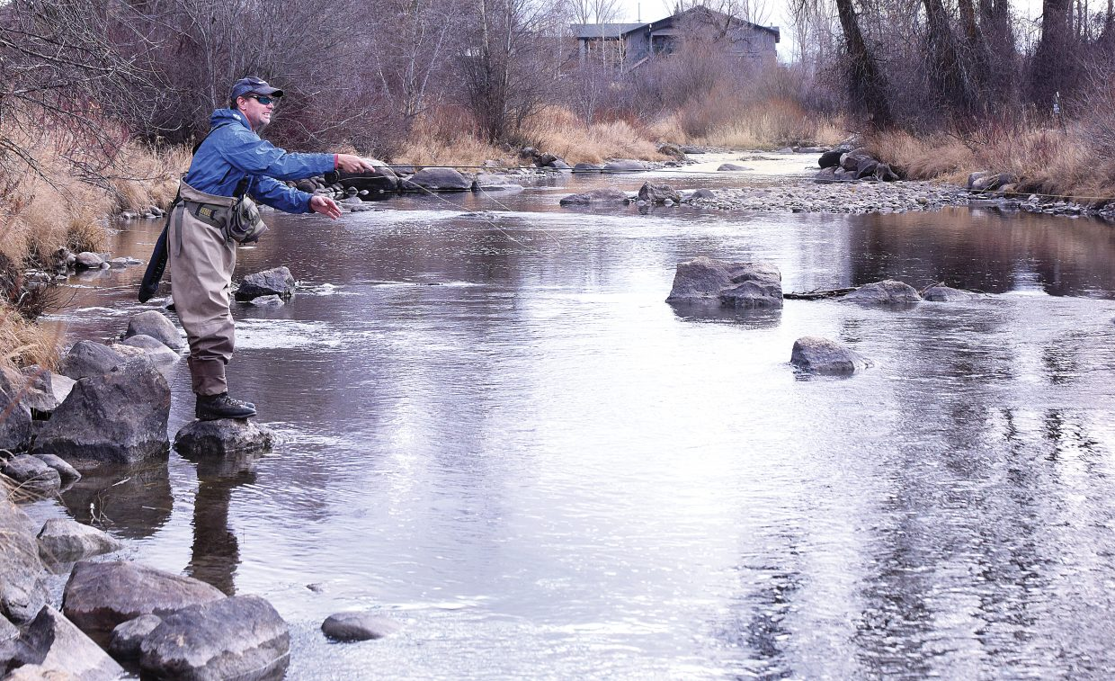 Steve Moos took advantage of Monday's unseasonably warm weather to do a little fly fishing on the Yampa River. Local skiers and snowboarders are hoping things cool off a bit tonight as crews at Steamboat Ski Area continue working to make snow for Opening Day on Wednesday.