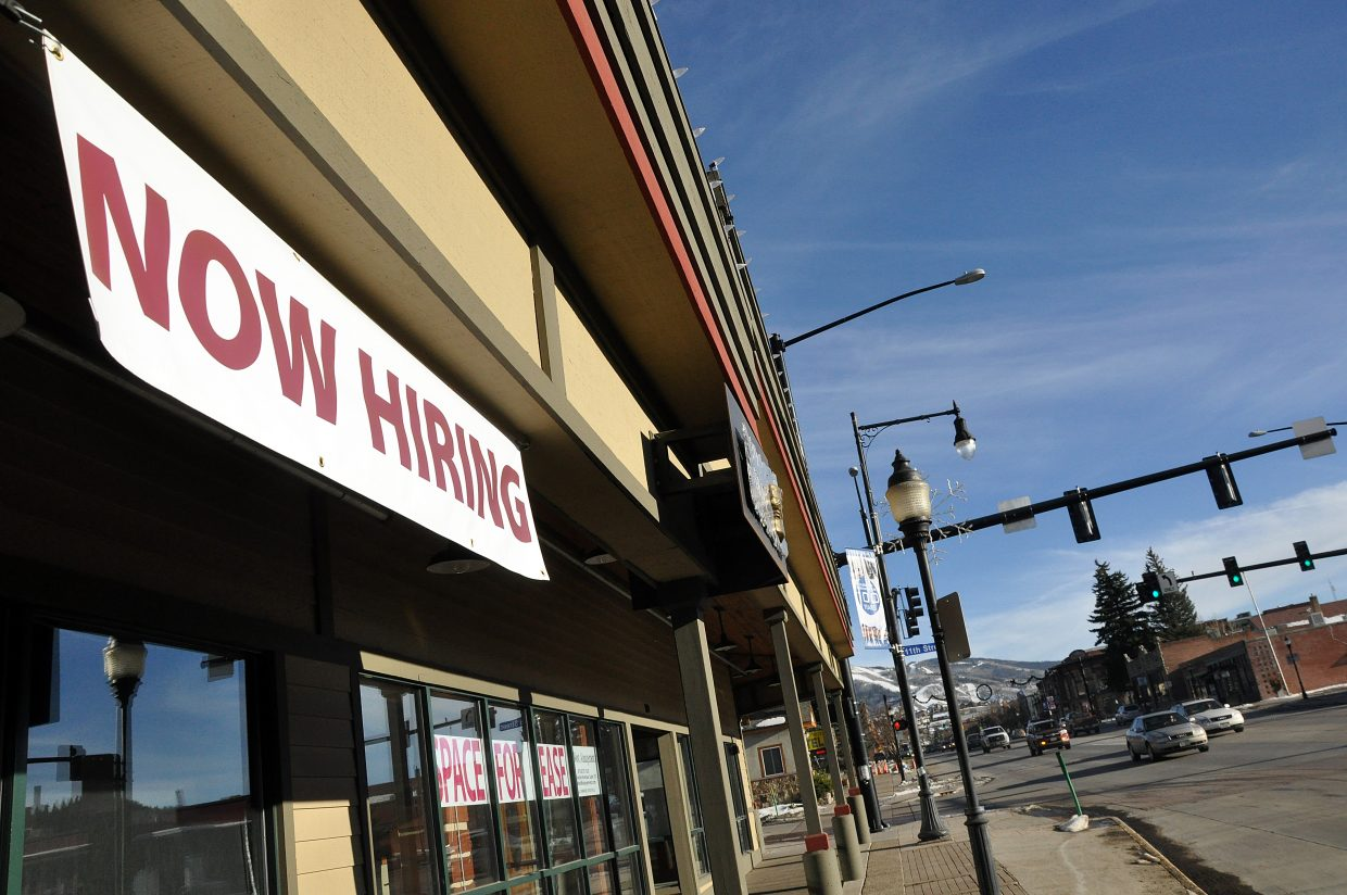 """A large """"Now Hiring"""" banner is displayed above Riggio's Italian restaurant in downtown Steamboat Springs. A lower unemployment rate and higher housing prices are creating challenges for local employers."""