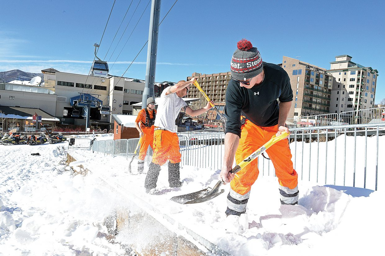 Snowmaker Travis Scott and fellow employees move snow off the Magic Carpet at the base of the Steamboat Ski Area in 2015.
