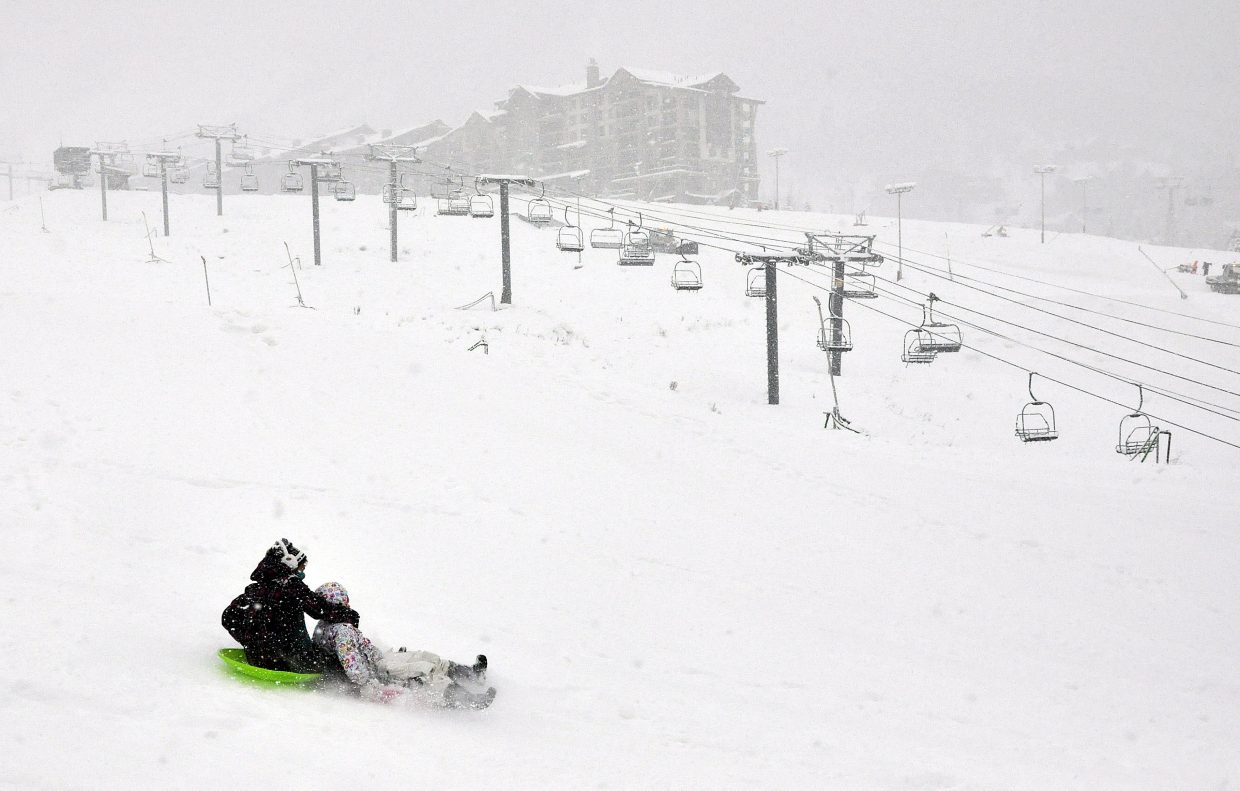 Morgan and Ainsley Ochoa sled at the base of Steamboat Ski Area on Tuesday afternoon as mountain crews make final preparations for Scholarship Day. The ski area is opening 655 acres, which encompasses 22 percent of the ski area's terrain.