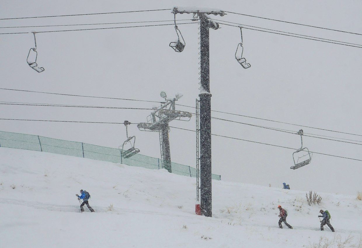 The snow falls down as the skiers skin up Mount Werner.