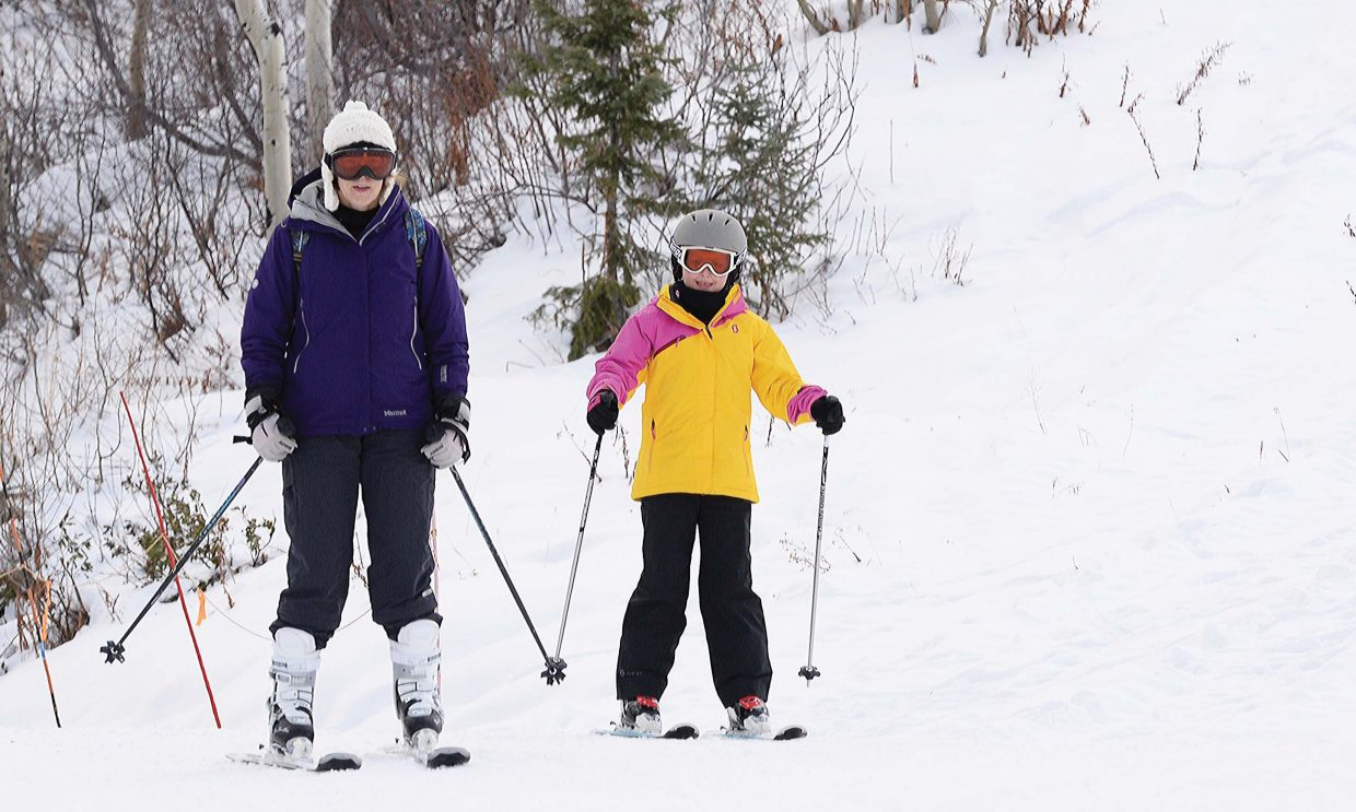 Vivian Gaz and her daughter, Emma, from Pennsylvania, ski down Why Not ski run Wednesday during Scholarship Day at the Steamboat Springs Ski Area. The annual fundraiser for the Steamboat Springs Winter Sports Club marks the start of the season. The proceeds raised from the sale of lift tickets are donated to the Steamboat Springs Winter Sports Club's scholarship program.