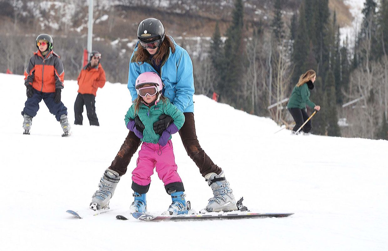 Kellie Babcock helps her daughter, Bronwyn, ski on the beginner terrain at the base of the Steamboat Ski Area Wednesday during Scholarship Day. The ski area sold lift tickets for $30 for the entire mountain or $20 for the bottom on the first official day of the season. The proceeds are donated to the Steamboat Springs Winter Sports Club's scholarship program.
