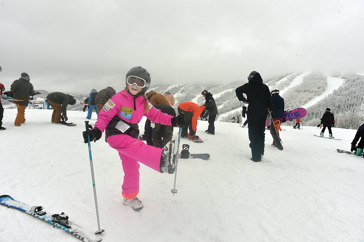 Nine-year-old Neve Wade stretches out the muscles outside the gondola building at mid-mountain Wednesday before making the first runs of the 2014-15 season at Steamboat Ski Area. The ski area opened for business with Scholarship Day —a annual fundraiser for the Steamboat Springs Winter Sports Club's scholarship program. Excited skiers hoped for great snow conditions after a storm earlier this week, but the day did not live up to expectations after temperatures warmed up during Tuesday evening.