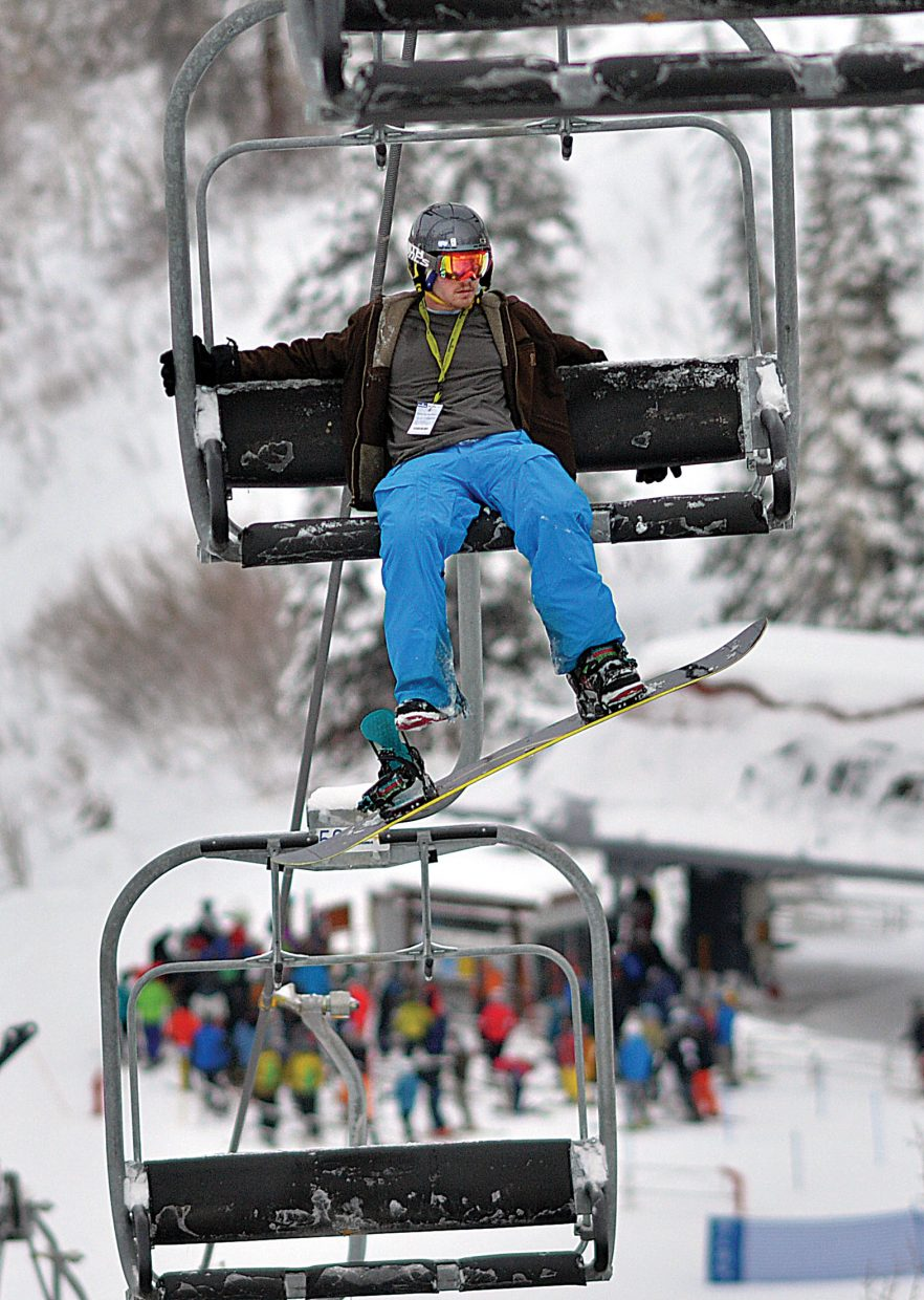 A crowd can be seen forming in the Storm Peak Express lift line as snowboarder Matt Quick takes a few minutes to relax as he heads up the Burgess Creek lift at Steamboat Ski Area during Scholarship Day in 2014.