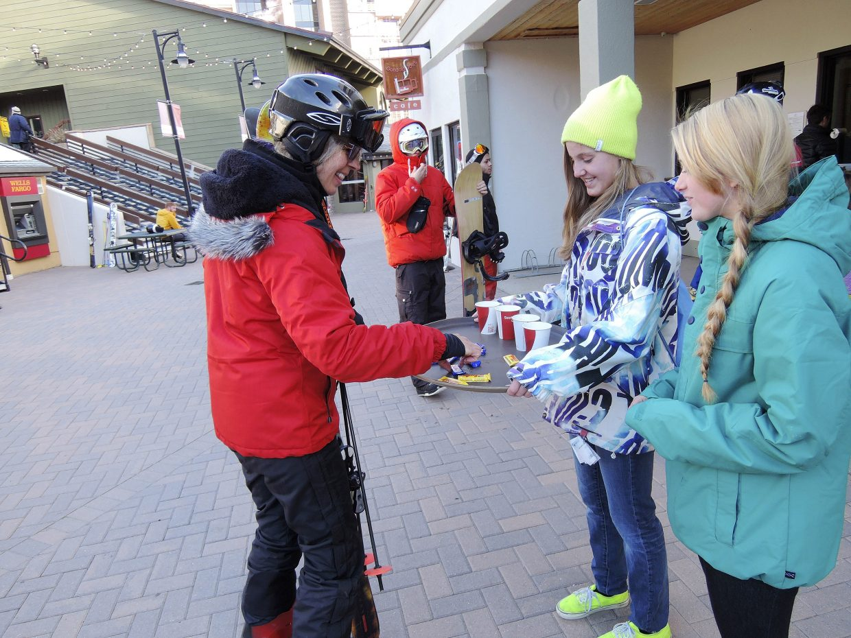 Steamboat Springs Winter Sports Club snowboarders Savanna Atkins, right, and Ocoee Wilson serve candy and chocolate to Steamboat skier Deb Brabenec on Wednesday morning during Scholarship Day at Steamboat Ski Area.