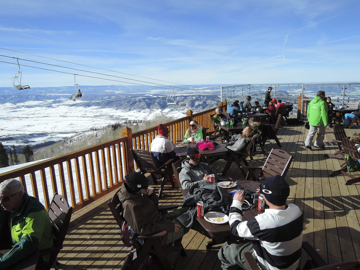 People sit on the deck Wednesday at the new Four Points Lodge at Steamboat Ski Area.