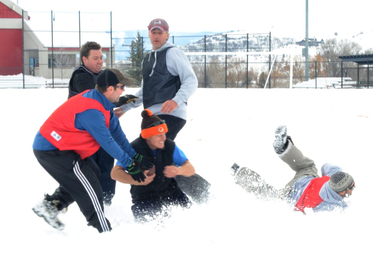 Tom Brodman gets tackled during the fifth annual Turkey Bowl on Thursday at Ski Town Fields.