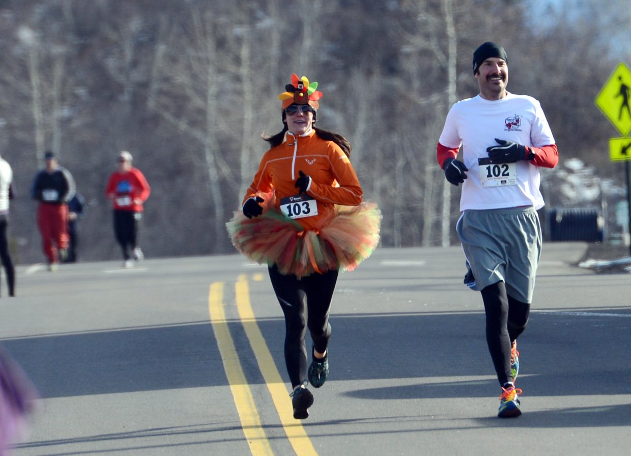 Jessica Sword, left, and Chris Sword close in on the finish line during Thursday's Turkey Trot in Steamboat Springs.