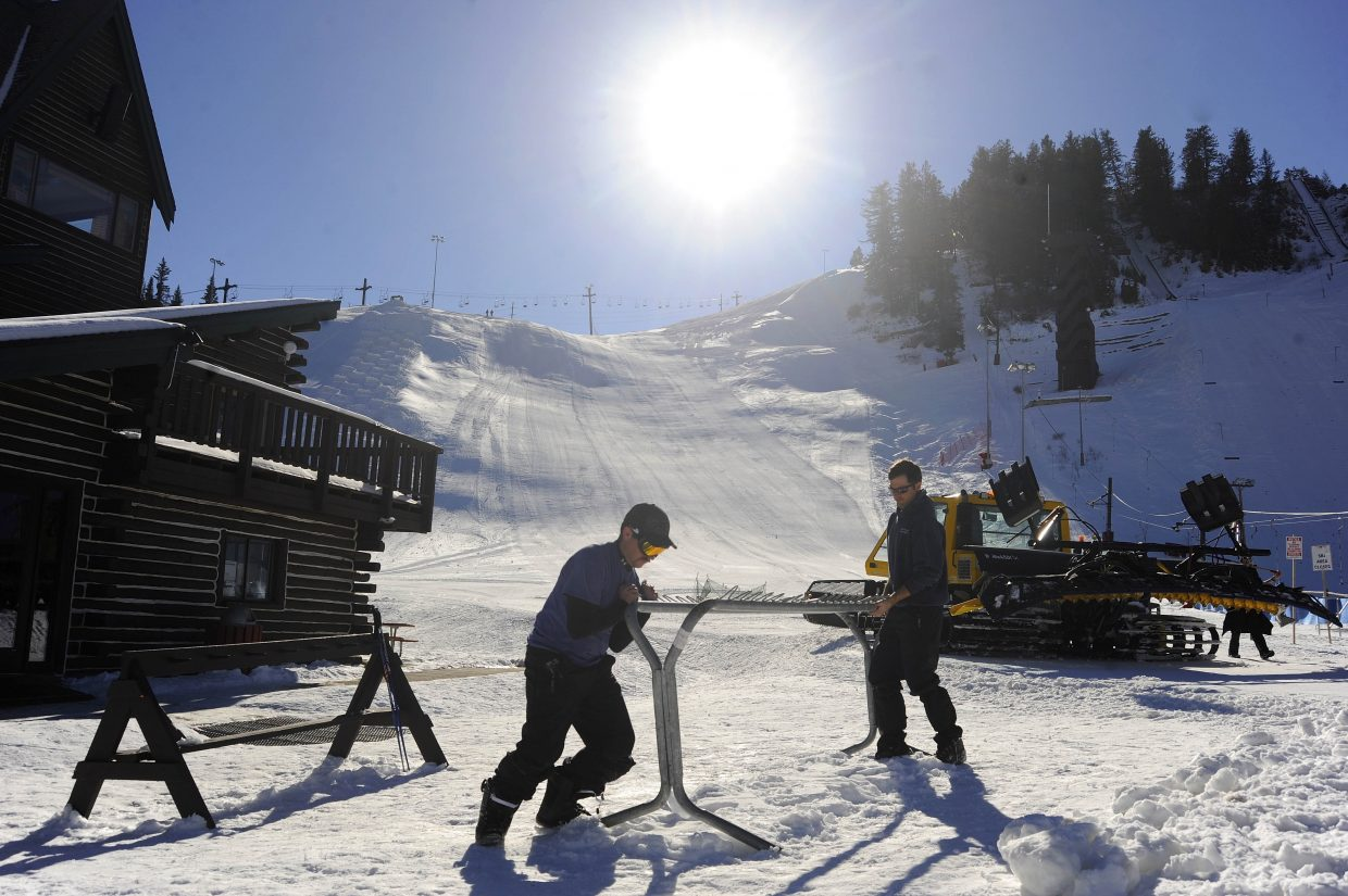 Marc Bell, left, and Brad Setter move a ski rack while preparing Howelsen Hill Ski Area for its opening day Saturday.