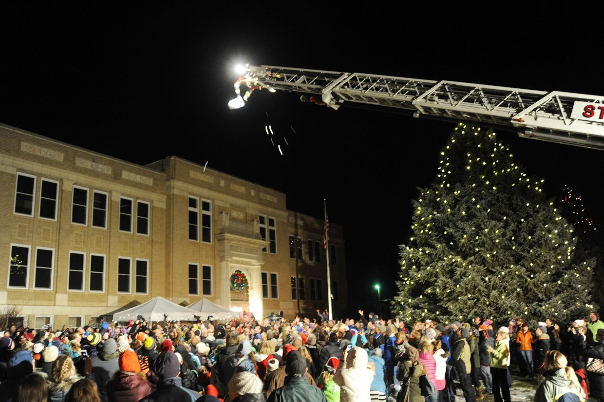 Pingpong balls with coupons for downtown businesses are dropped from a fire truck ladder Friday night during the Light Up the Night community tree lighting ceremony at the Routt County Courthouse.