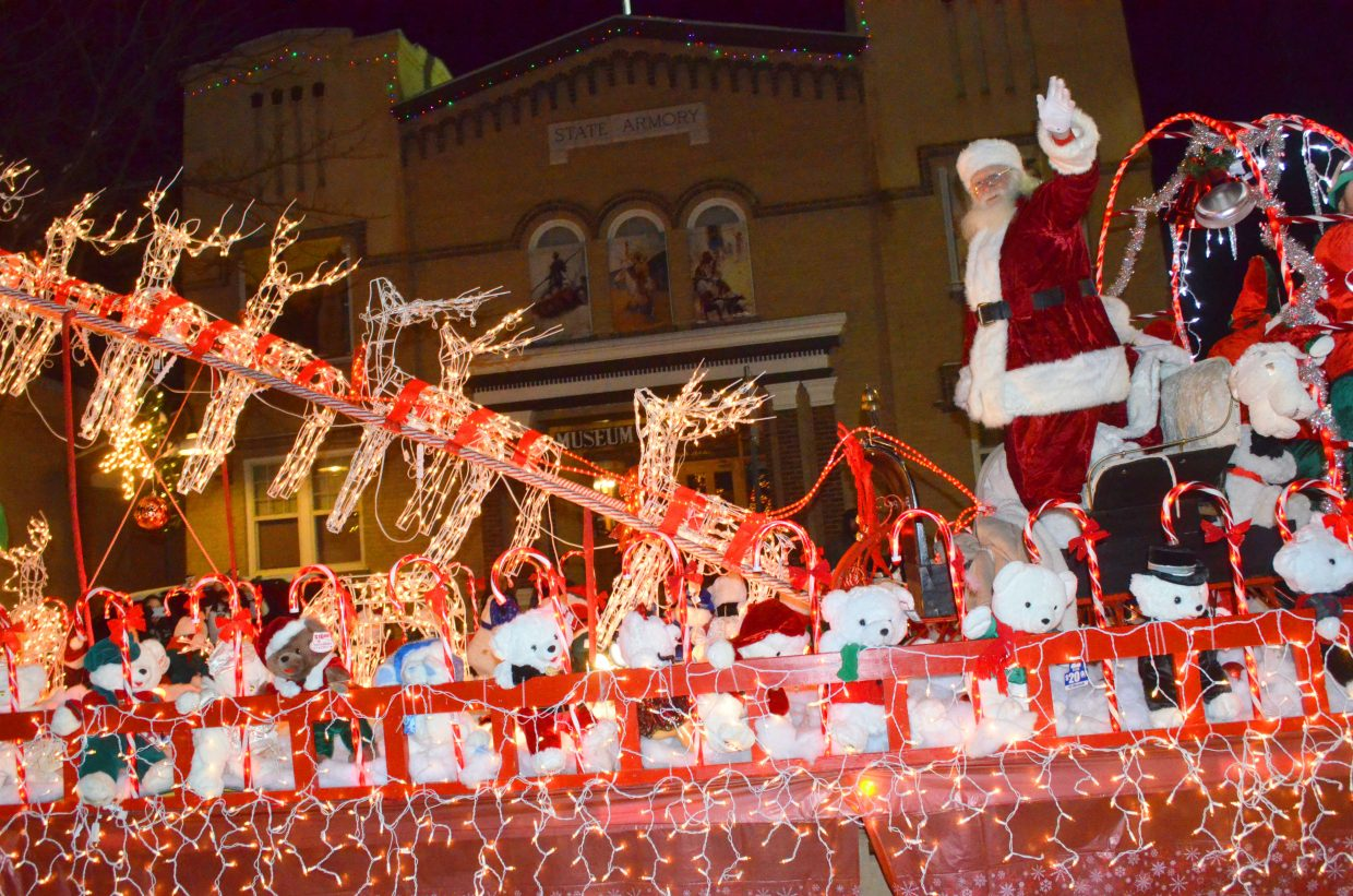 Santa Claus waves to the crowd from his float, the final entry in the Parade of Lights, hosted by Downtown Business Association Saturday night in Craig. The route included many holiday-themed characters headed down Yampa Avenue and Victory Way, concluding with a parade glow in the parking lot of the former Safeway building.
