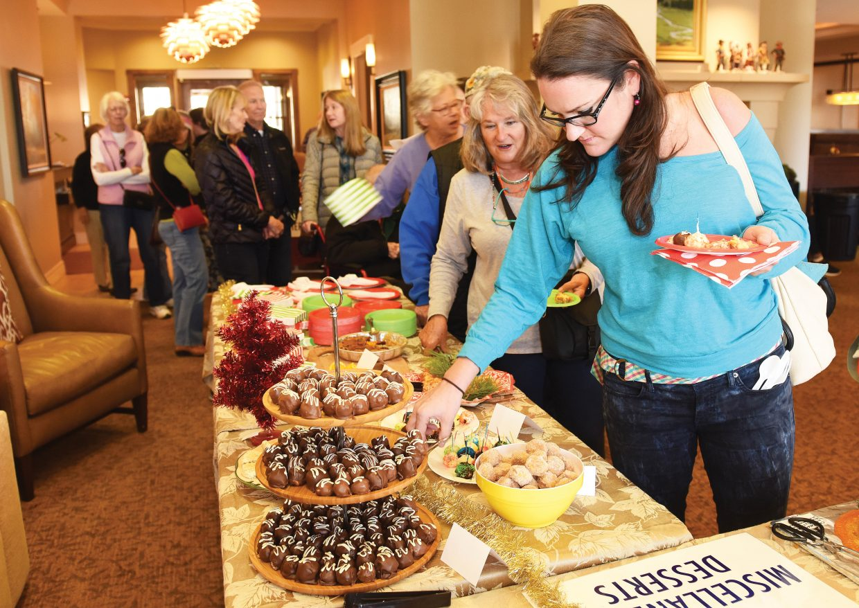 Julie Horace makes her way through the line at the during the annual Holiday Dessert Bake-Off at Casey's Pond Monday afternoon. Two hundred people showed up for the opportunity to taste 35 different treats.