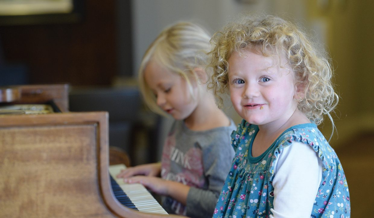 Hawkins Garner spends a few minutes at the piano with buddy Harlow Kuntz at Monday's Holiday Dessert Bake-off at Casey's Pond. The cookie crumbs on Harlow's face let everyone know she had tried some of the treats at the dessert table.
