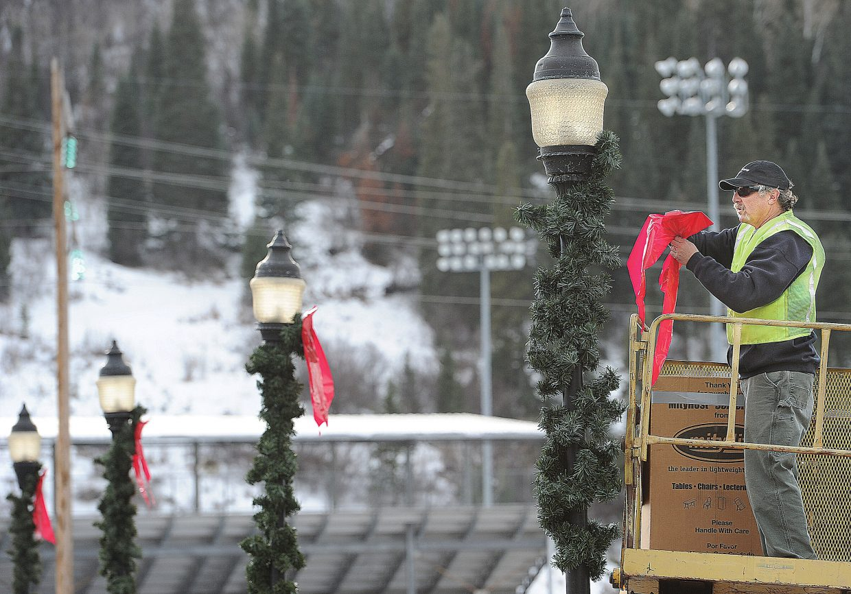 Ernie Jenkins, Parks supervisor for the city of Steamboat Springs, hangs holiday decorations on the Fifth Street bridge Monday afternoon.