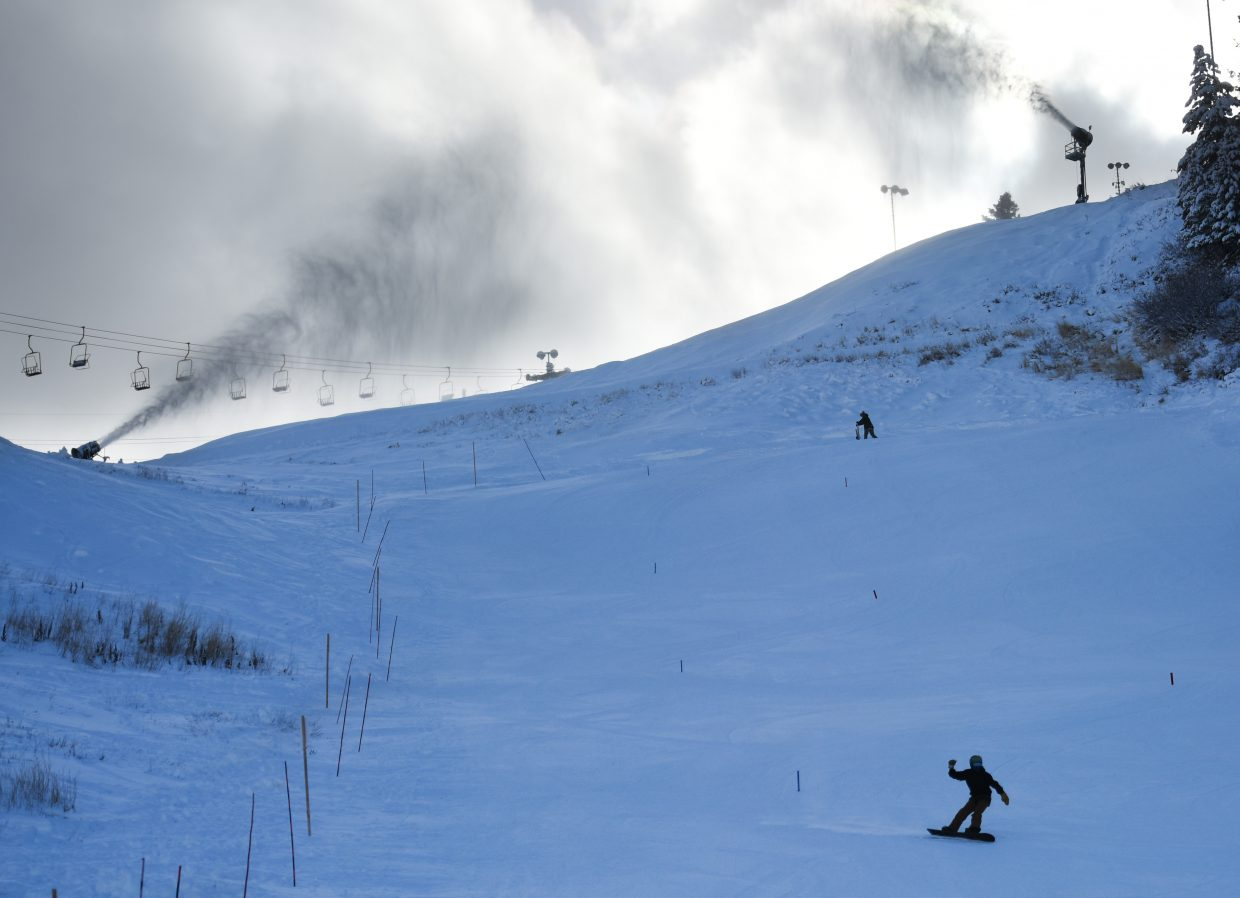 Looking for the fresh stuff: Members of the Steamboat Springs Sports Club snowboard cross team train on the face of Howelsen Hill Wednesday afternoon while snowguns pump new snow onto the slopes above them.