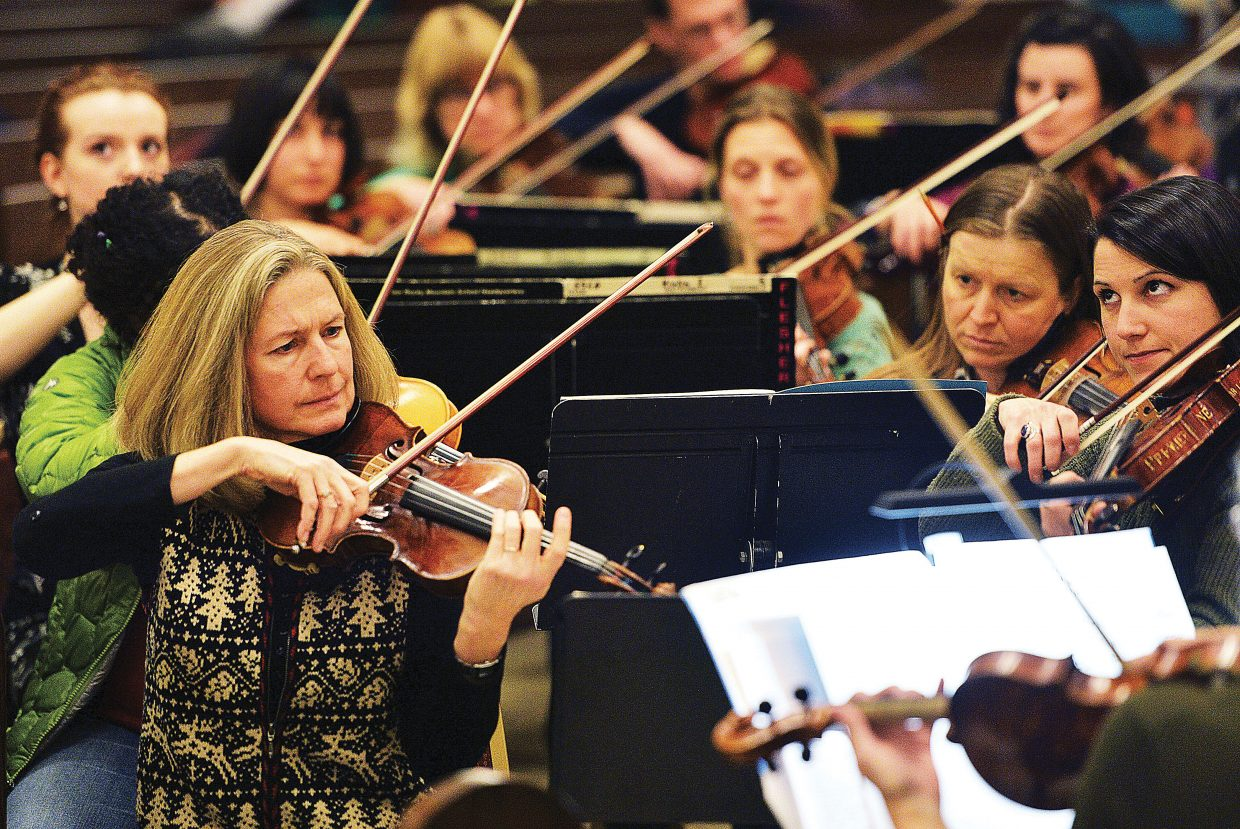 Teresa Steffen Greenlee, center, plays on Wednesday evening with the Steamboat Symphony Orchestra during a rehearsal at the Holy Name Church for the Christmas Spectacular. The Christmas Spectacular will take to the stage at the Strings Music Pavilion at 7 p.m. Saturday and 4 p.m. Sunday.