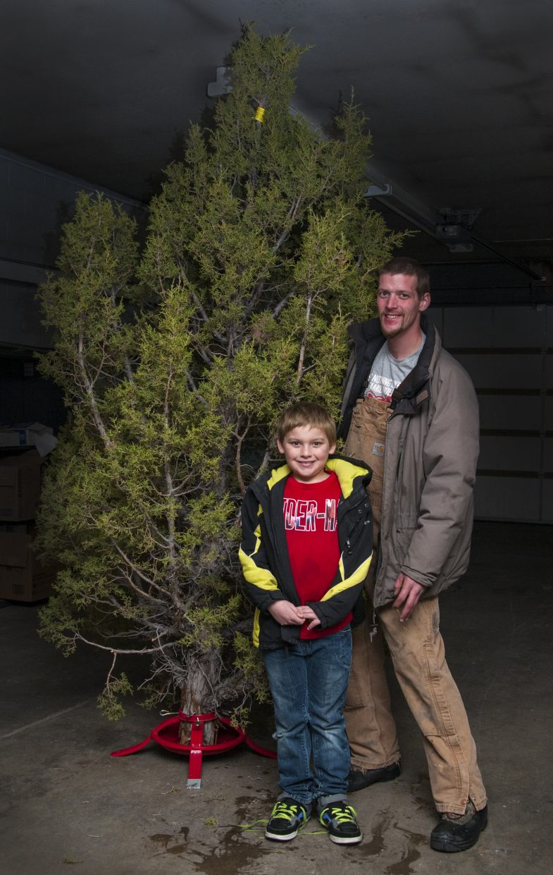 Craig residents Jesse Smith-Golden and 9-year-old Sean Smith pick up their Christmas tree Friday, gifted to them by the Craig Daily Press with the help of Love INC. The juniper tree was harvested from public lands in Western Moffat County as part of the Bureau of Land Management's Christmas tree permit program.
