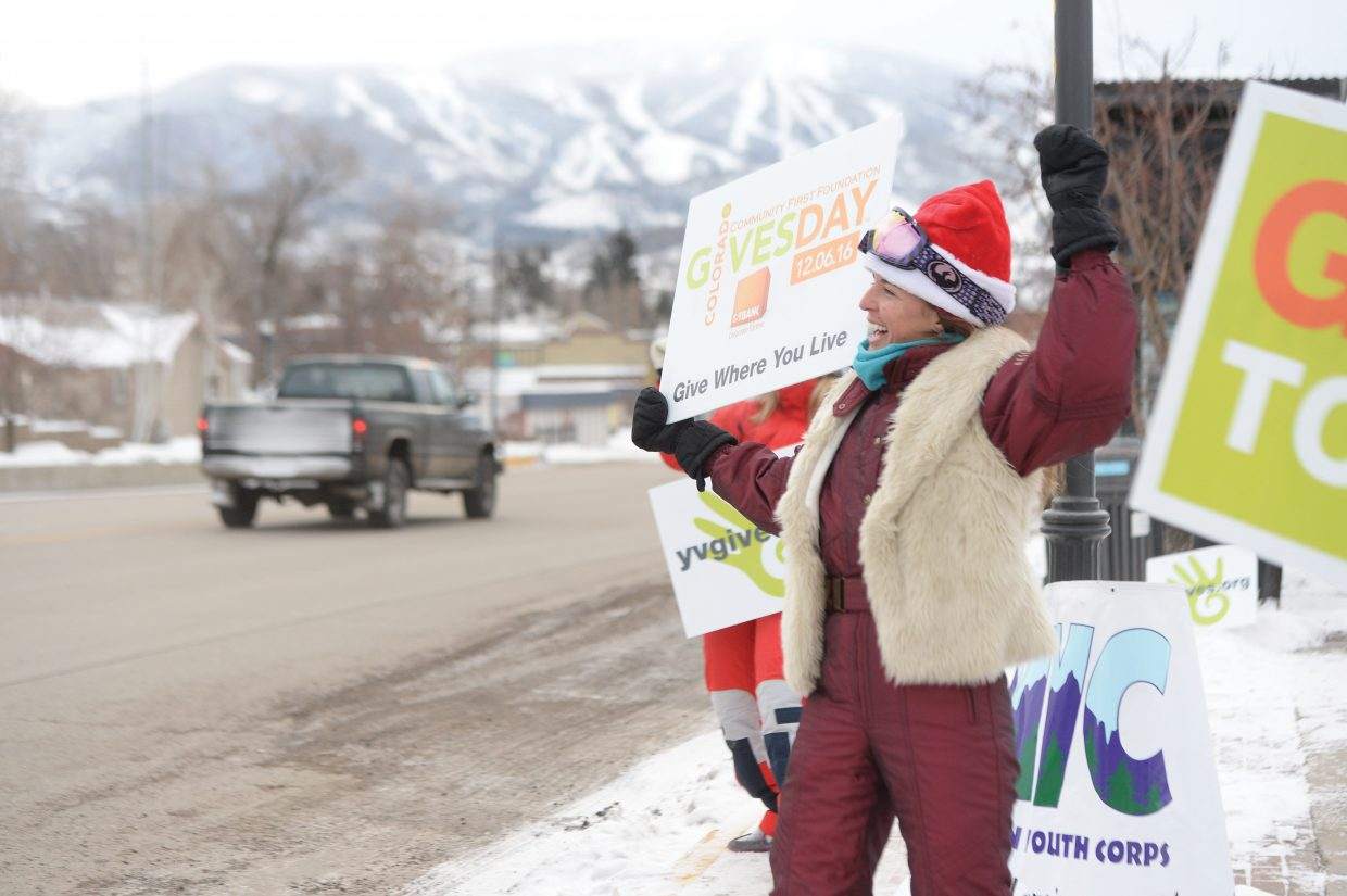 Laraine Martin braves the cold temperatures outside as she gets passing drivers to honk while waving signs a the corner of Lincoln Avenue and 13th Street in Steamboat Springs Tuesday morning. Martin, who is with the Rocky Mountain Youth Corps, was out promoting Yampa Valley Gives and Colorado Gives Day.