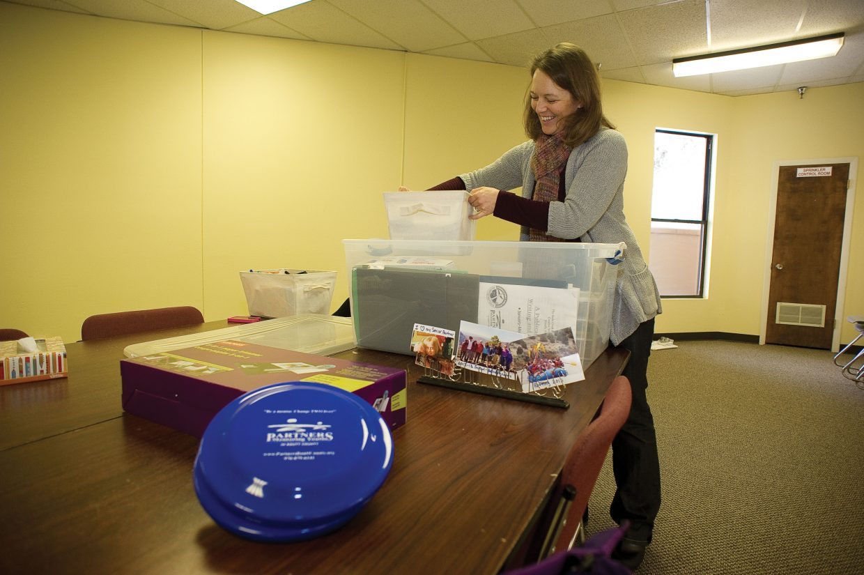Becky Slamal, community outreach director for Partners of Routt County, unloads boxes in the organization's new office space in Sundance at Fish Creek.