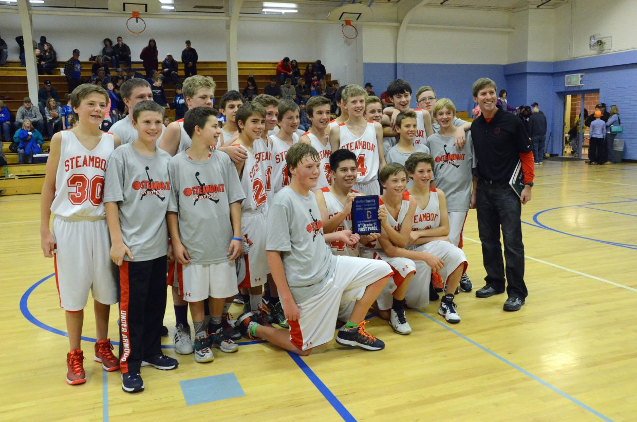 Coach Chris Adams and the members of the Steamboat Springs Middle School eighth-grade boys basketball A-team hold high their ceremonial plaque after winning the district tournament Saturday at Craig Middle School. The Sailors narrowly beat the Bulldogs, 24-23, in the championship round to claim first place.